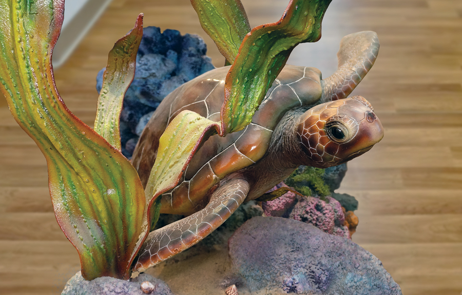 Closeup of a realistic sculpted turtle surrounded by seaweed and coral