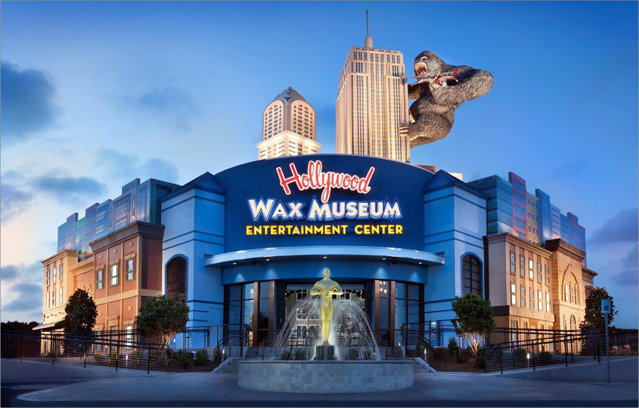 Exterior of the Hollywood Wax Museum at night showcasing the custom signage, giant sculpted skyscrapers and gorilla