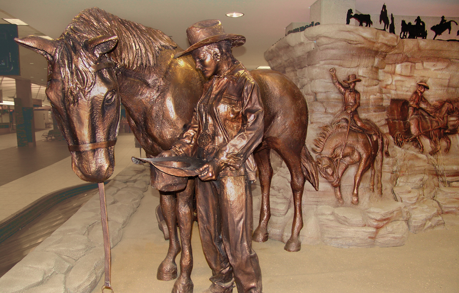 Museum exhibit showcasing custom bronze sculptures of cowboys, horses and badlands