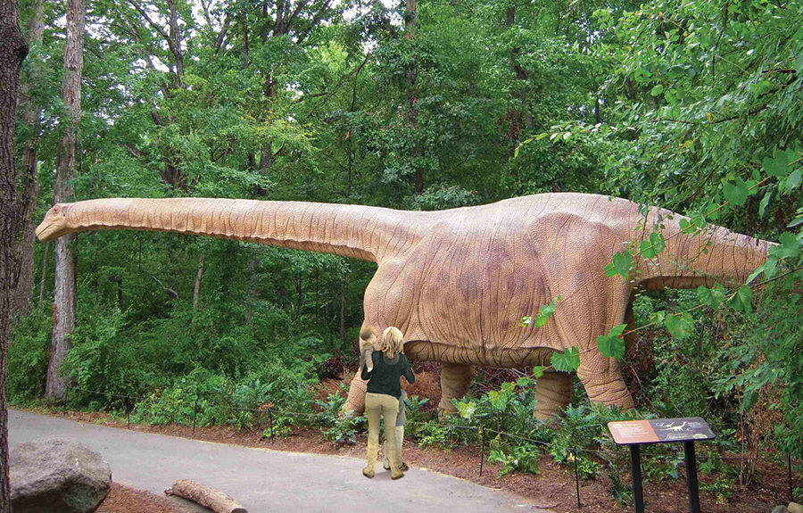 Realistic statue of giant dinosaur in an outdoor zoo exhibit