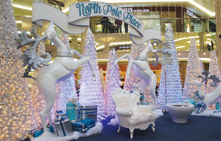 Christmas themed mall décor with sculpted reindeer, trees and ribbon signage