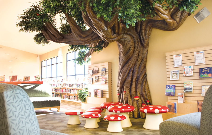 Public library with sculpted foam trees and mushroom stools for kids