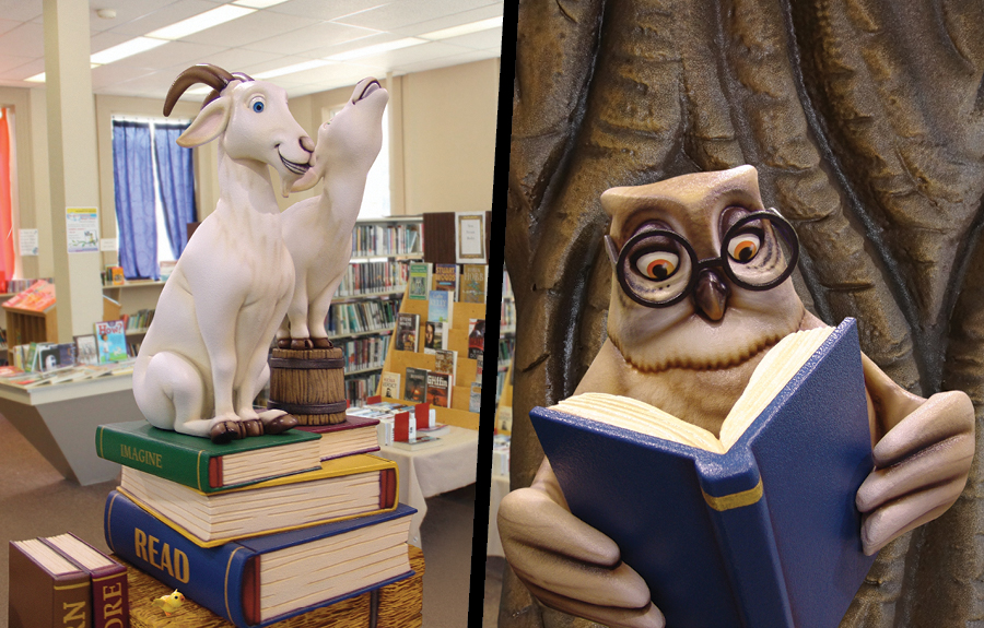 Sculpted giant books with goat characters and a reading owl in a kids library