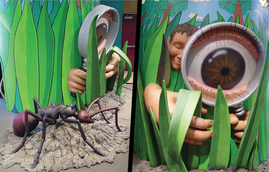Giant 3d foam ant, grass, and magnifying glass in a kids science centre