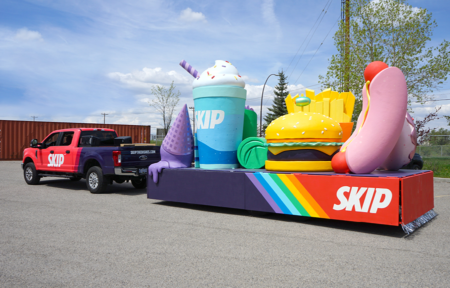 Skip the Dishes parade float featuring colorfully painted and sculpted food