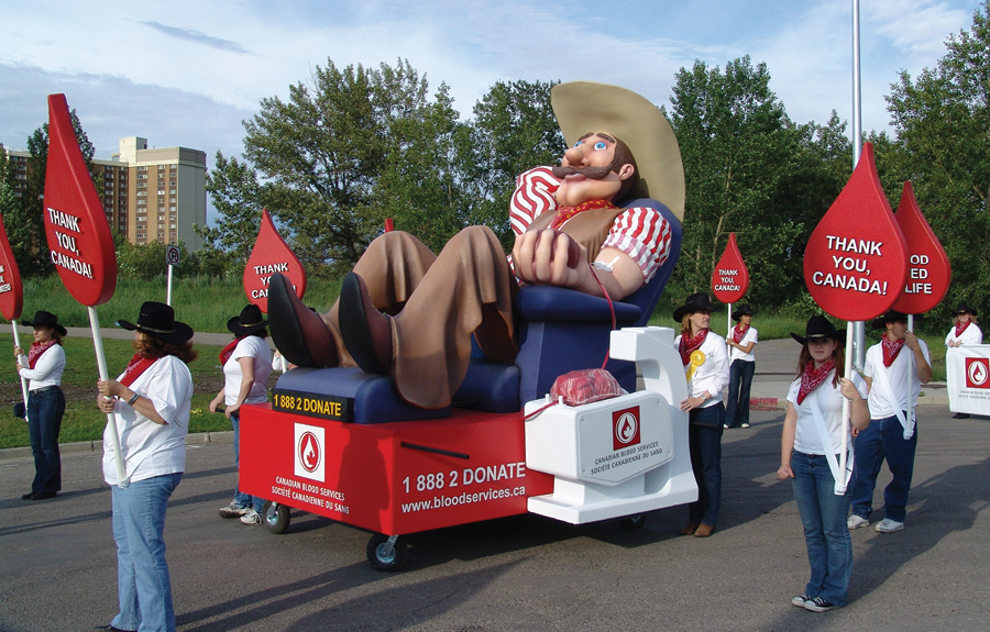 Stampede Parade float for Canadian Blood Services with a sculpted cowboy character giving blood