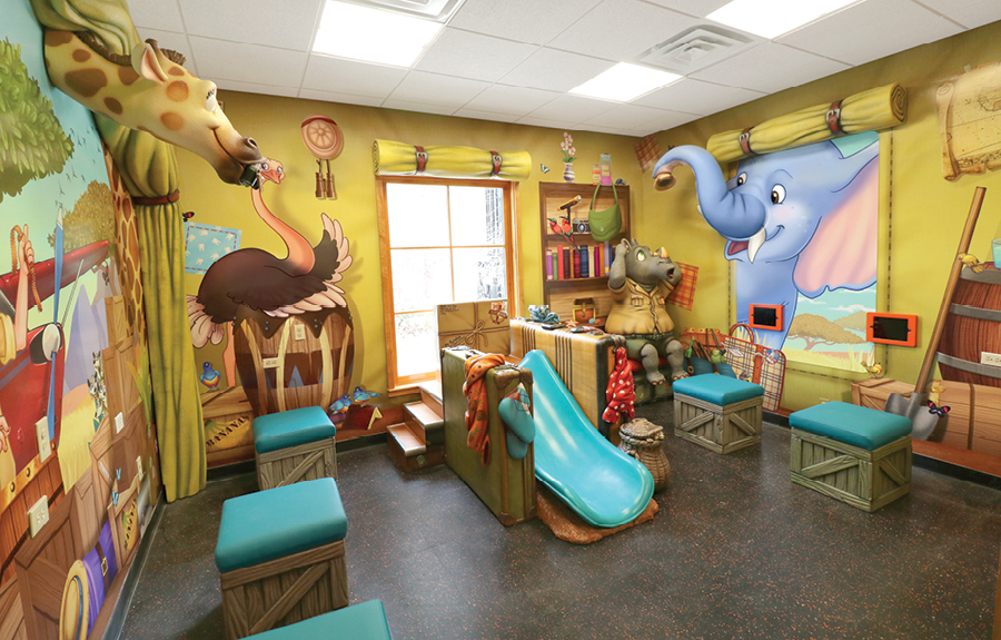 Safari adventure themed kids play area with sculpted animals, stools and custom murals