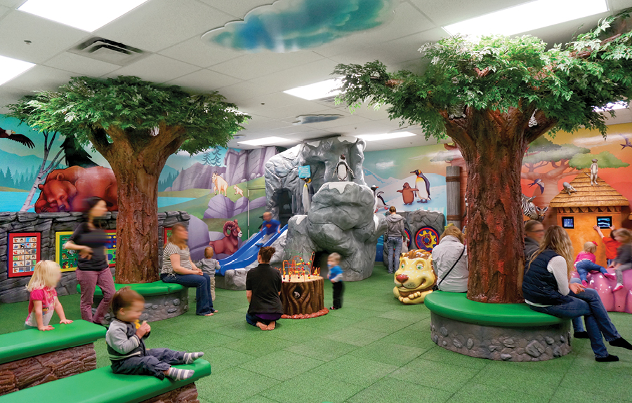 A mall kids play area with sculpted trees, play structures, and wall mural modeled off of the local zoo