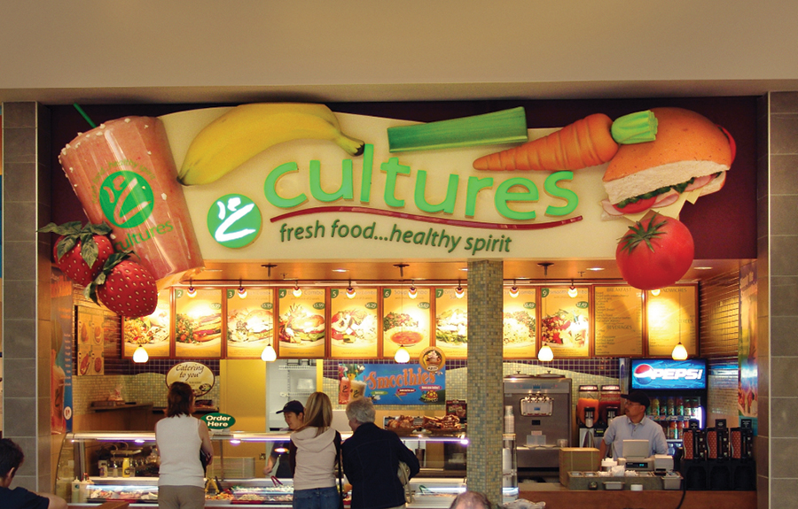 Food court vendor signage with giant sculpted fruits and vegetables