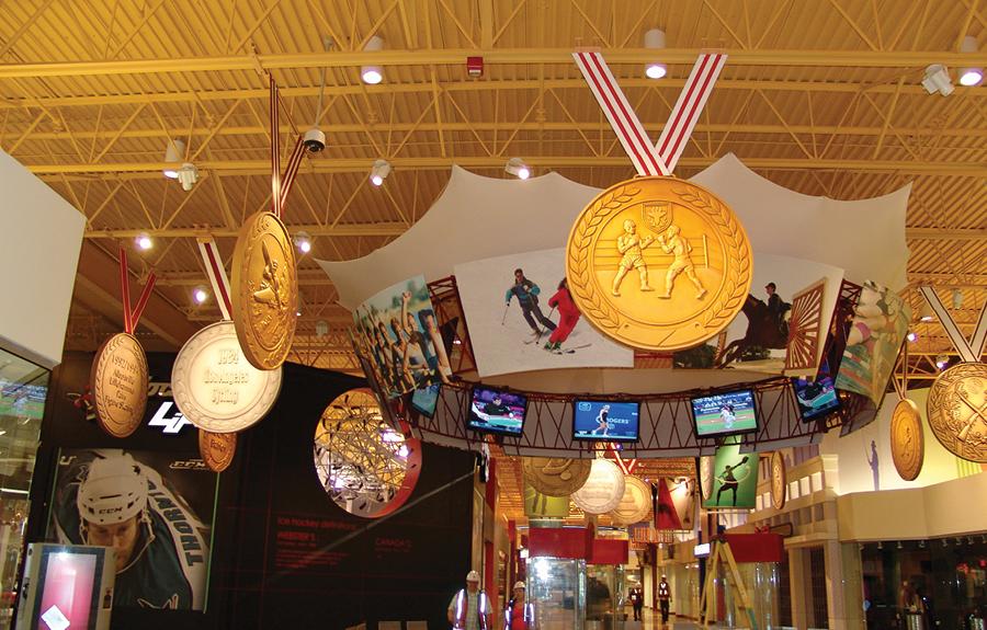 Large foam props of sports gold medals on display in a mall resting area