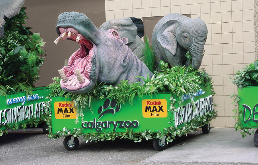 Parade floats for a zoo featuring  sculpted african animals and foliage